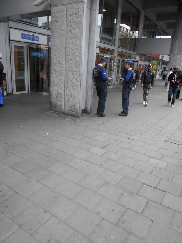 Deux policiers en embuscade devant Partena, dissimulés derrière un pilastre