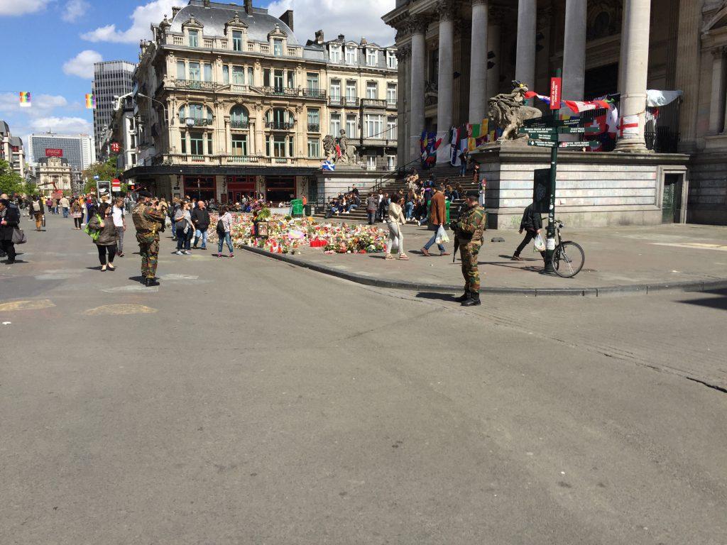 Deux soldats de faction devant la Bourse : celui de gauche s'occupe en prenant des photos...